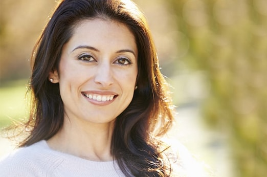 A woman standing outside shows off her smile to illustrate our expertise in General & Cosmetic dentistry in Redmond, WA.