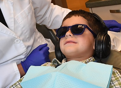A young patient in the dental chair wearing noise canceling headphones and sunglasses to help him relax during treatment.