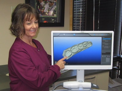 Diana, a Dental Assistant at Frost Family Dental, shows a patient their digital X-Ray.