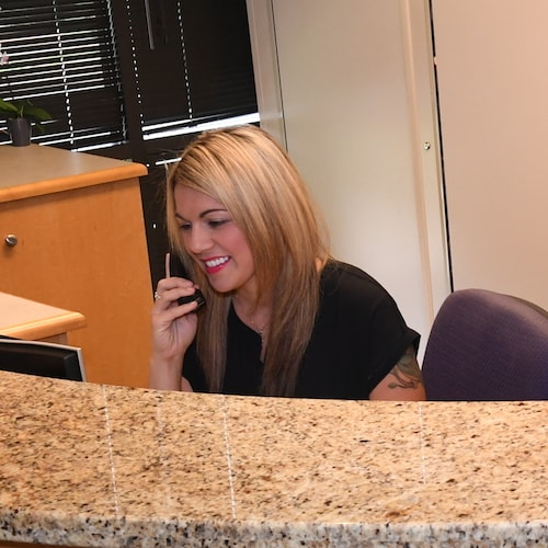 Jene at the front desk of Dr. Frost, our dentist in Redmond, to show how we do Same-Day Emergency Care.