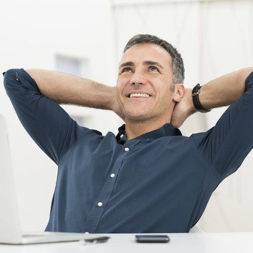 A man leans back in his chair with his arms behind his head to illustrate the anxiety-free dentistry at Frost Family Dental.