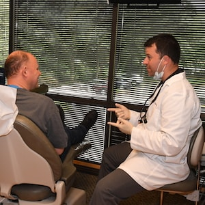 Dr. Dan Frost talks to a patient about his dental care in our Redmond practice.