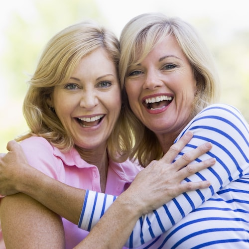 Two woman embrace and smile to illustrate our rewards program.